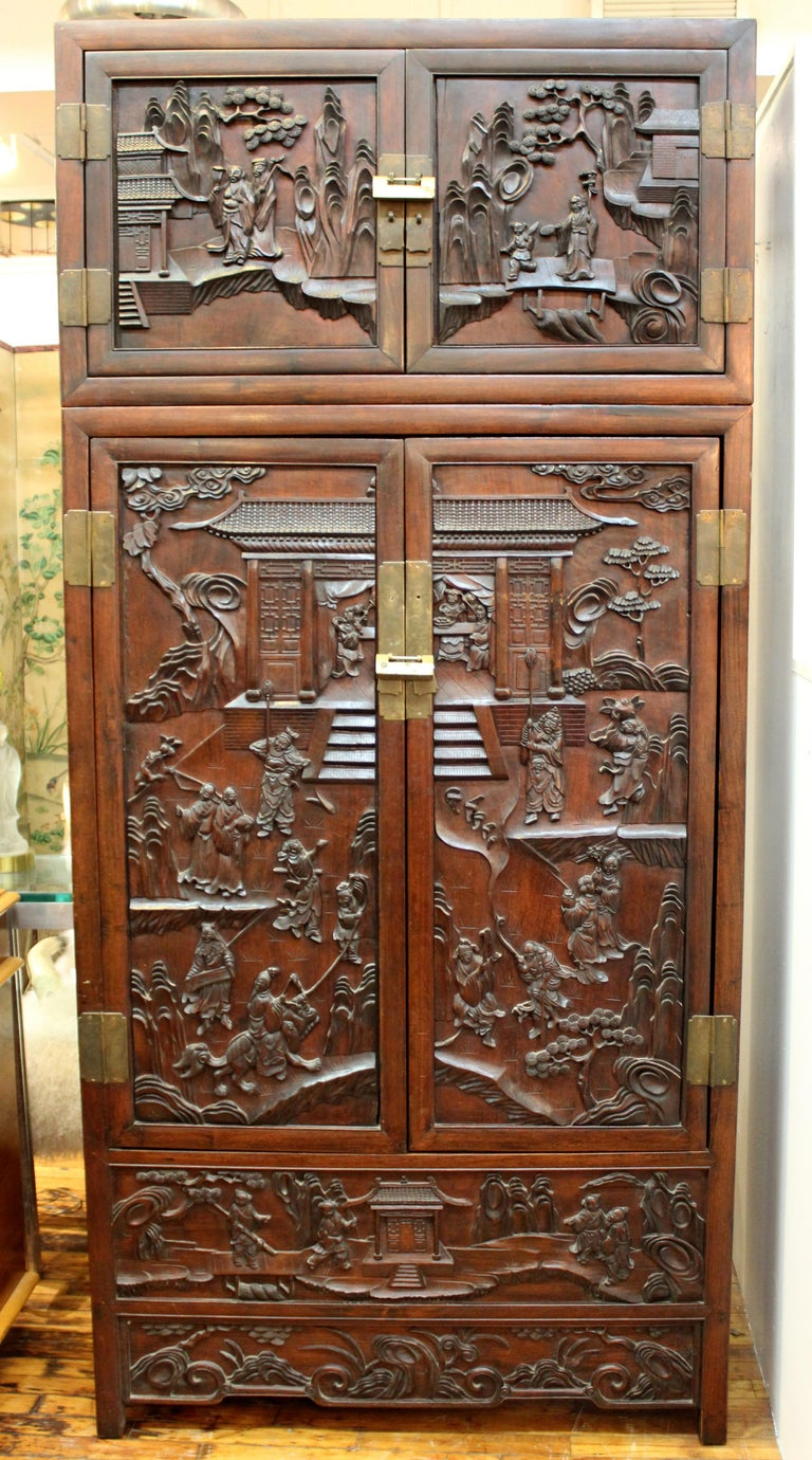 Chinese 19th century pair of zitan wood cabinets and hatchets made with elaborately hand-carved high-relief scenes. Each cabinet has a hatchet on top with square panel doors. The Fine carved scenes depict landscapes inhabited by people and animals