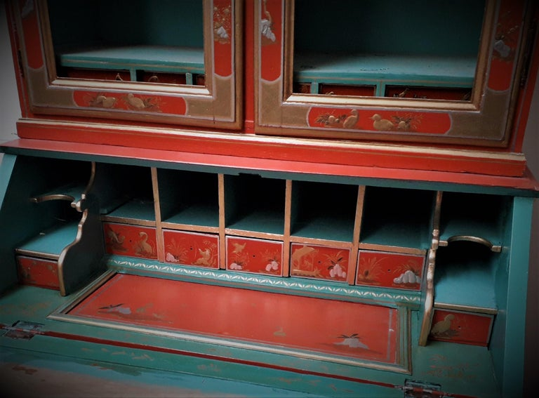 Chinoiserie Red Lacquer Bureau Bookcase.  The shelved upper part with double broken arched doors opening to reveal a part fitted interior with lower small drawers, more Chinoiserie scenes decorate the fitted bureau interior with a slide top hidden