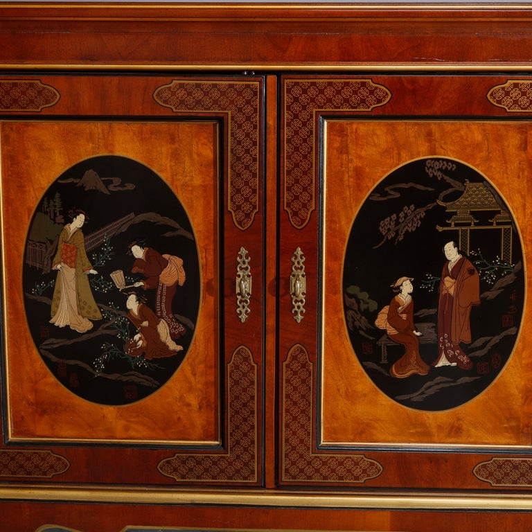A chinoiserie decorated credenza by Drexel offers mahogany construction with double door case having burl panels with reserves of hand painted figures in countryside setting ebonized ground, interior with shelving and drawer, gilt highlights
