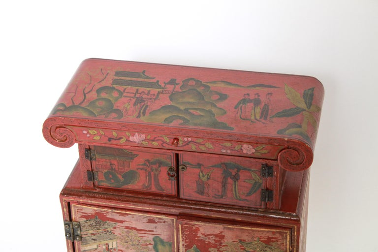Chinoiserie red and figural painted diminutive cabinet with two small doors over two larger doors, interior drawer and one at top.