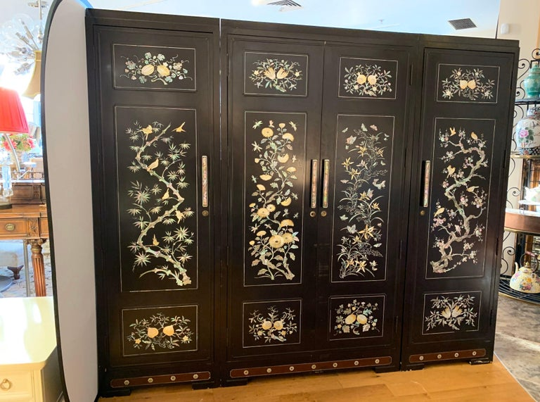 Extra large, three-piece chinoiserie black lacquer wardrobe cabinet complete with drawers and hanging rods.