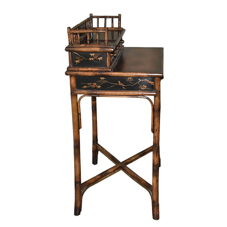 A fine chinoiserie faux tortoiseshell handmade wood and bamboo desk with drawers and leather top. A rare find, it is in superb condition and a true testament to the craftsmanship of the 1800s. A small ledge at the top of the piece is decorated with