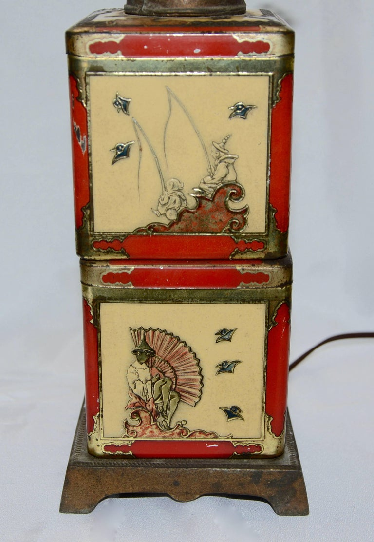 A pair of Asian antique tea tins make up this electric table lamp that was designed in the 1940s. The tins rest on a cast metal base. There are two different scenes on each tin. A cast metal piece with a faux key sits atop the tins and is completed