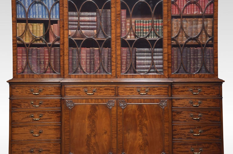 Chippendale Revival bookcase, the projecting breakfront molded cornice. Above four large astragal glazed doors opening to reveal an adjustable shelved interior. To the base section fitted with four frieze drawers with brass swan neck handles, above