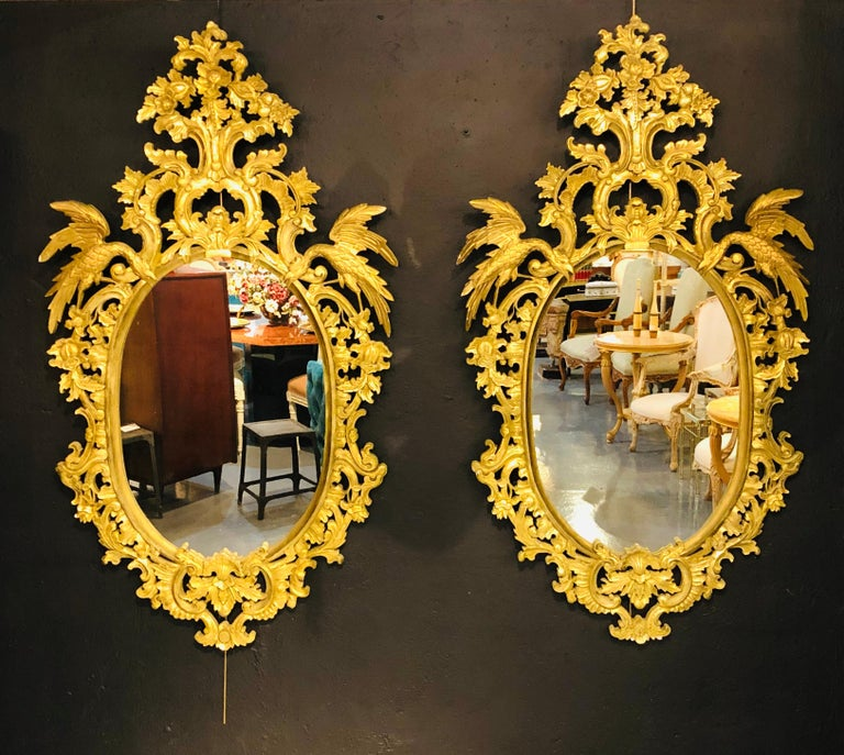 Pair of Chippendale style elaborate giltwood wall or console mirrors. The pair oval in form with a clean center mirror flanked by a finely carved carved frame of roses, floral design and scroll having full bodied winged birds perched on each side of