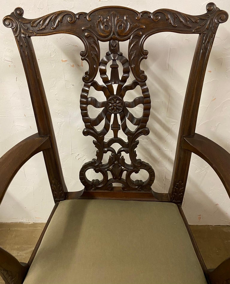 The circa 1900 Chippendale style mahogany armchair has hand carved designs including a back combining a motive of ribbons, a rosette, tassel and leaves. The arms end with eagle heads supported by uprights decorated with acanthus leaves. The front