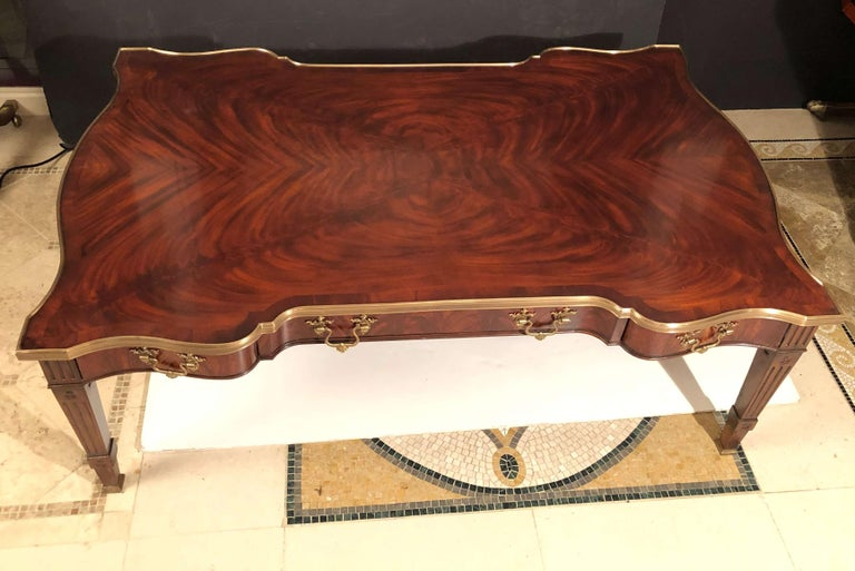A large Chippendale style flame mahogany veneer and solid cocktail table, the serpentine brass bound top above two drawers on each side centered by a leather inset slide drawer with a concealed drawer, all with brass Rocaille handles, on square