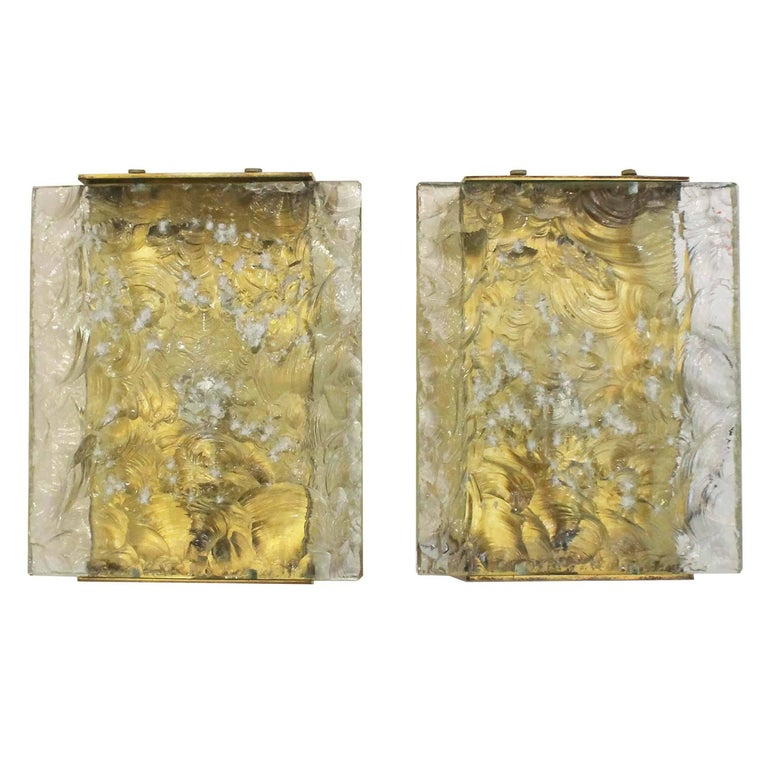 Eye catching sconces by Max Ingrand featuring hand chiseled glasses on a brass frame. On the side they are closed off by two cream colored glasses. Each holds one candelabra socket.