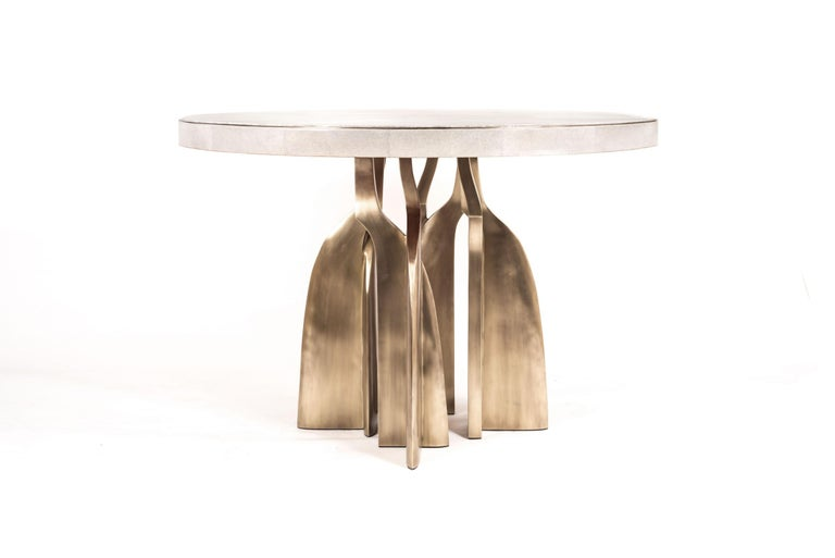 The Chital breakfast table is a stunning piece, a statement in any space. The cream shagreen inlaid top has a subtle metal inset around the frame, followed by bronze-patina brass sculptural legs clustered together as the base. This piece is designed