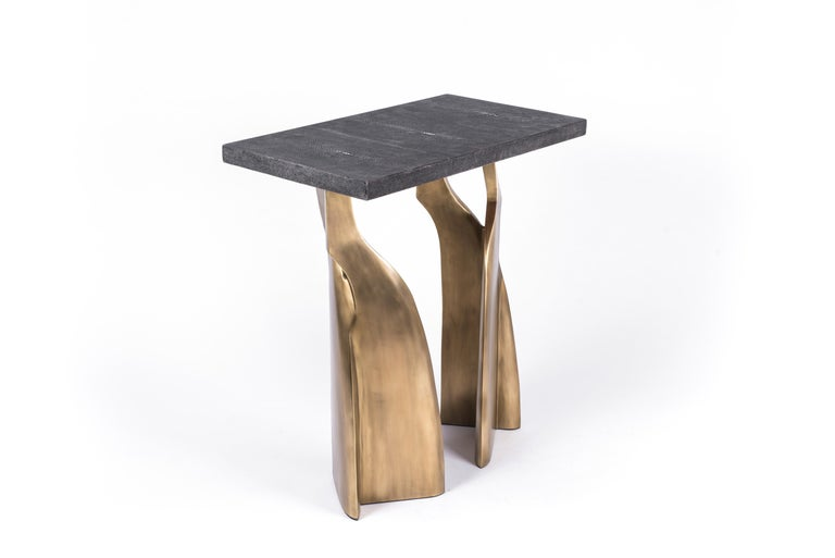 The Chital rectangle side table is both dramatic and organic it's unique design. The black shagreen inlaid top sits on a pair of ethereal and sculptural bronze-patina brass legs. This piece makes for the perfect end table and is originally inspired