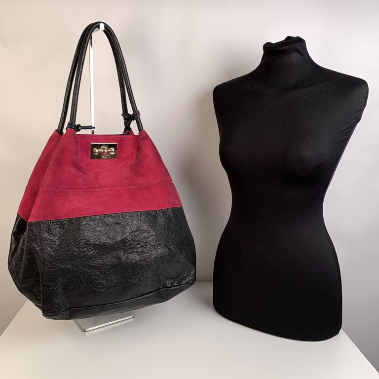 Large Chloe color block tote bag, crafted in black leather and magenta suede. Gold metal hardware. Double shoulder strap with tassels detailing. Front twist lock closure. The interior of the bag is in fabric with a zip pocket and an open pocket.