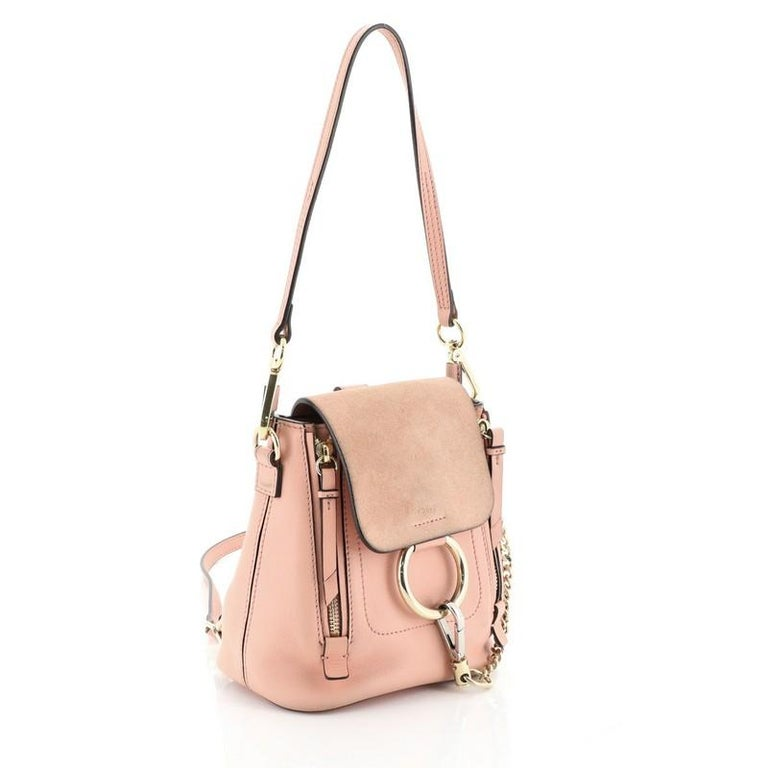 This Chloe Faye Backpack Leather and Suede Mini, crafted from pink leather and suede, features detachable flat top handle and shoulder straps, flap chain-clip and ring detail, expandable zip sides, and gold-tone hardware. Its flap opens to a neutral