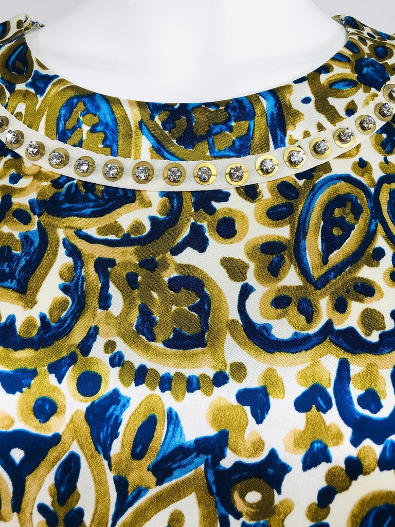 Chloe' gold and blue rhinestone jewel neckline blouse. Abstract print on a cream ground in blue and gold, the round neckline has a circular band of crystal rhinestones. 3/4 length sleeves have cuff vents. The blouse is hip length pull on style it