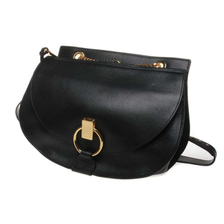 Chloe 'Goldie' shoulder bag in black calf leather and suede with gold-tone hardware. In a covetable shape inspired by the saddle, this bag features a main compartment with zipped top closure, a front flap pocket with ring and clasp fastening and an