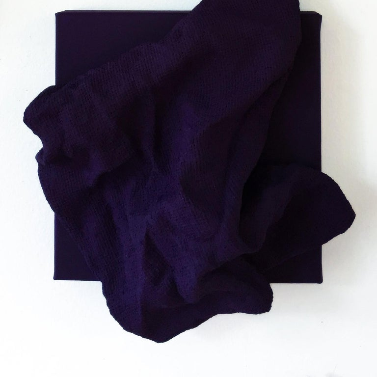 """""""Egyptian Violet Folds"""" is a pair of dark purple colored wall sculptures made with fabric on linen. The elegant folds are steadily built up and add intricacy to the structure. This creates a dynamic artwork where light circulates on the surface and"""