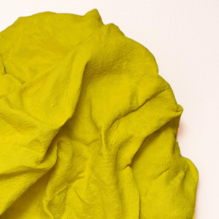 """""""Electric Yellow Folds"""" is a fluorescent yellow colored wall sculpture made with burlap on linen. The folds are carefully arranged from a single piece of burlap. This creates a dynamic artwork where light circulates on the surface and shadows are"""