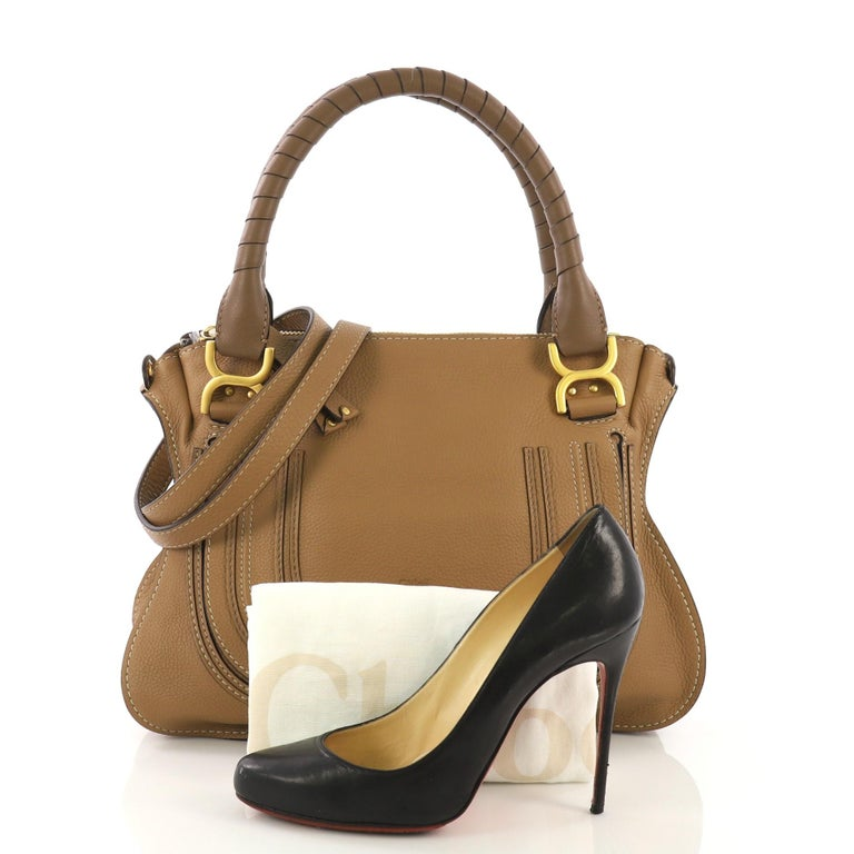 This Chloe Marcie Satchel Leather Medium, crafted in brown leather, features wrapped leather handles, horseshoe stitched on front flap, and gold-tone hardware. Its top zip closure opens to a green fabric interior with zip and slip pockets. **Note: