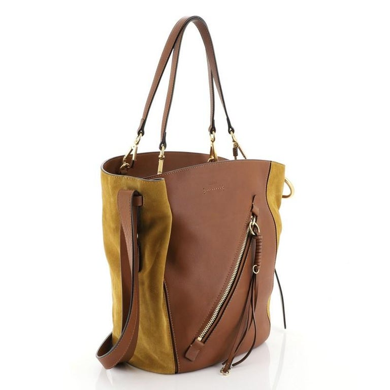 This Chloe Myer Tote Leather and Suede Medium, crafted from brown leather and suede, features flat leather strap, exterior front zip pocket, and gold-tone hardware. Its zip closure opens to a neutral fabric interior with zip and slip