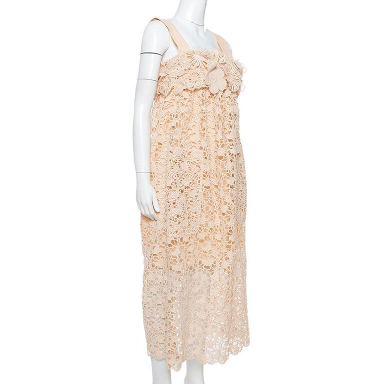 A delicate lace exterior with floral motifs meets a soft pale orange hue to characterize this feminine midi dress by Chloe. It has a sleeveless silhouette, a flattering empire waistline, and a comfortable fit. It is perfect for summer outings. Pair