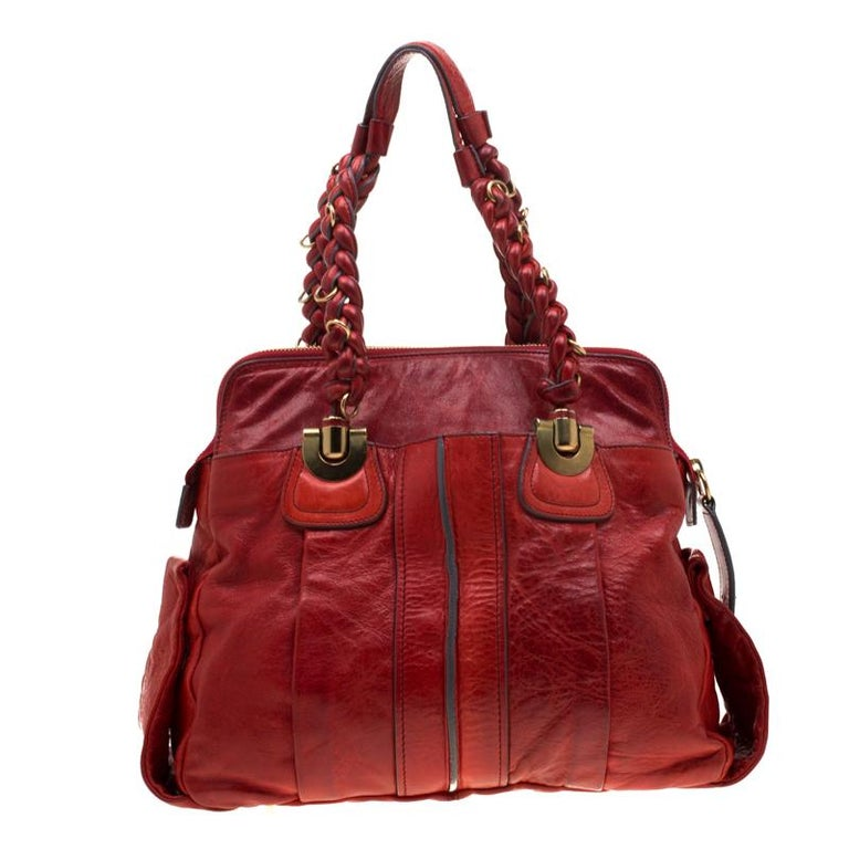 Get yourself this good-looking Heloise bag from Chloe for a posh look. The bag has been crafted from red leather and features dual braided handles. The zip closure opens to a fabric lined interior that will hold all your daily essentials. High on