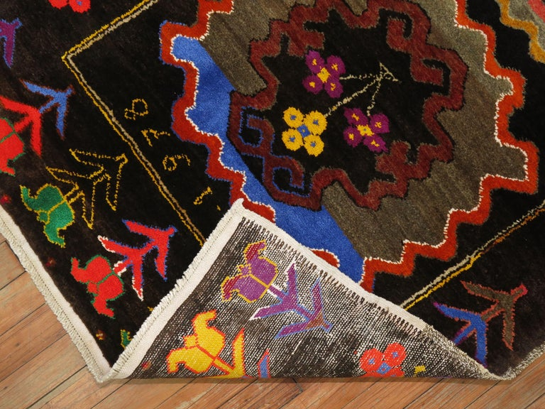 An eclectic Turkish Anatolian runner with a flashy array of electric colors. 5 medallions occupy a chocolate brown ground, bright coral, orange, green, yellow, blue and purple accents.    Measures: 3'3