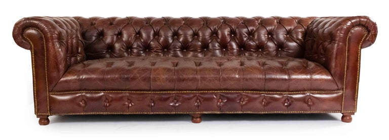 English Victorian style chocolate brown tufted leather Chesterfield sofa with distressed finish and out-scrolled arms on four wooden bun feet. Brass rivets along trim.