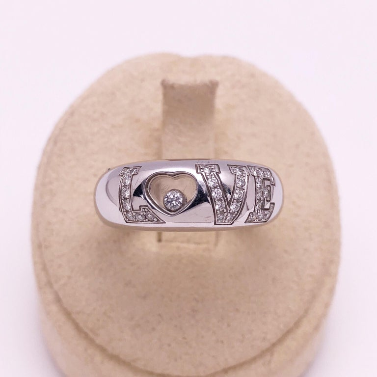 Chopard's iconic LOVE ring in 18KT white gold. The LOVE  is spelled out and set with round brilliant diamonds. A single floating diamond floats in the heart shaped O. 28 diamonds =0.24carats 1 diamond =0.05 carats Size 6.75 Style # 82/2899-20 Serial