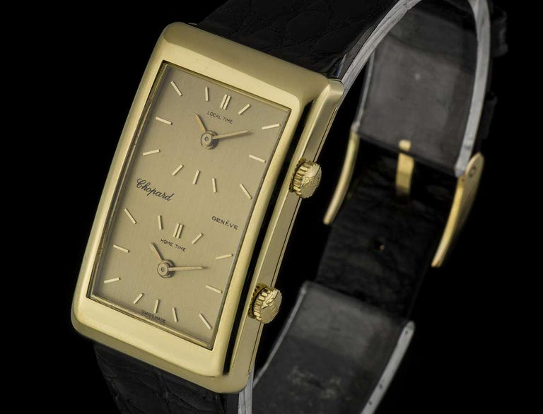 An 18k Yellow Gold Dual Time Zone Gents Wristwatch, champagne local time and home time dials with applied index batons, an 18k yellow gold fixed polished bezel, a brown leather strap (not by Chopard and not as pictured) with a gold plated pin buckle
