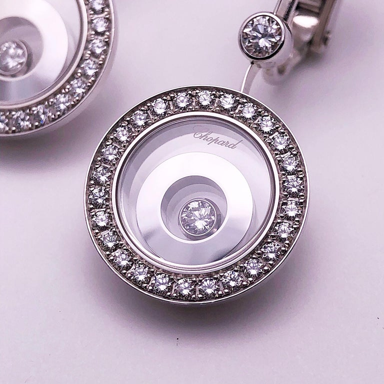 A modern twist on Chopards iconic floating diamond collection. These earrings are from the Happy Spirit group.  The earrings are designed with a single round hi polished white gold circle that sits on the ear. A round bezel set diamond forms the
