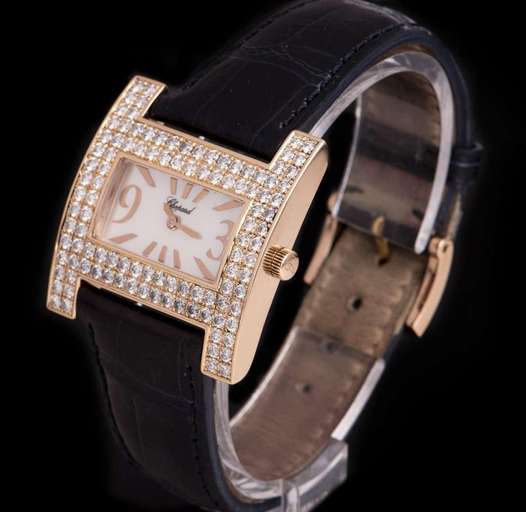 An 18k Rose Gold H Ladies Wristwatch, mother of pearl dial with applied hour markers and applied arabic numbers 3 and 9, a fixed 18k rose gold bezel set with 108 round brilliant diamonds (~2.71ct), an original navy blue leather strap with an