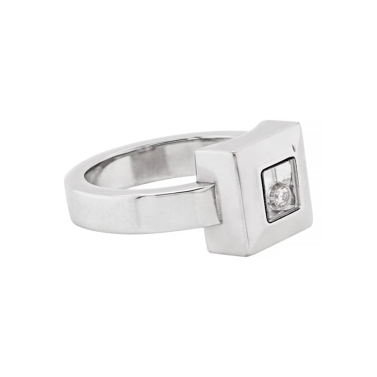 This beautiful Chopard Happy Diamond Icons ring is crafted from 18 carat white gold and features an elegant square frame measuring 1 x 1cm. The Chopard's signature mobile 'happy diamond' is placed between a pair of sapphire crystals which are set in
