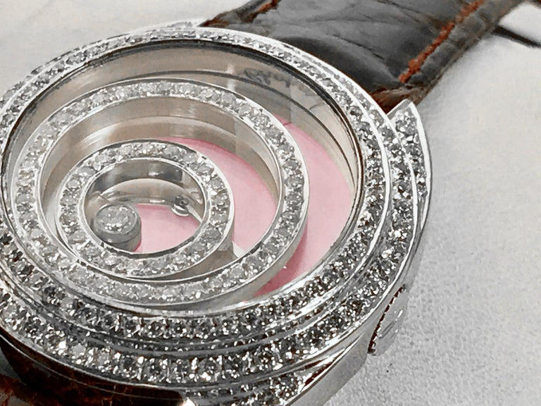 This absolutely gorgeous Chopard Happy Spirit ladies quartz wrist watch is a visual stunner. The dial is a beautiful light pink mother of pearl and is fitted with a custom floating diamond halo set that all articulate and move while your wrist is in