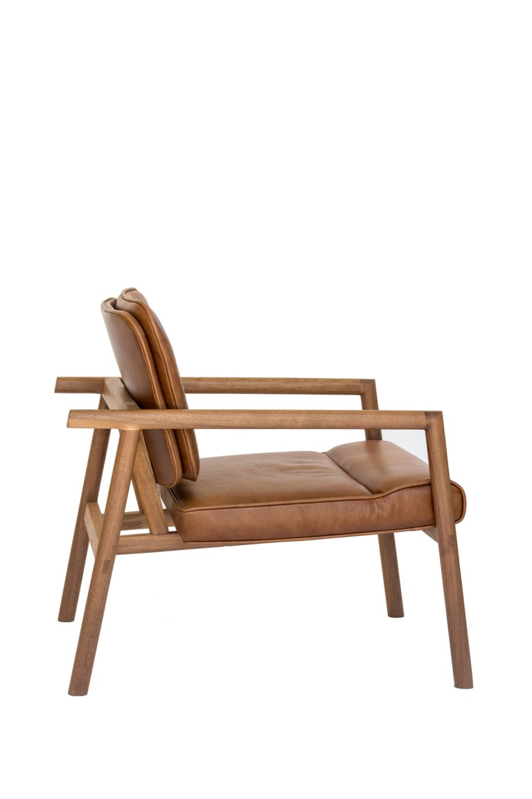 Solid wood construction with hand-cut joinery and custom upholstered seat and seat back. This chair shown in walnut and camel leather.  In stock leather choice: black, olive, camel or vegan leather. Wood choice: ebonized oak, walnut, natural oak