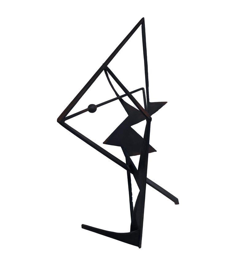 This dynamic table sized sculpture is created from cut steel shapes, welded together in an abstract geometric pattern patinaed to a soft black with bits of the natural rust peeking through. While the work adheres to a rigid, rational geometry, this