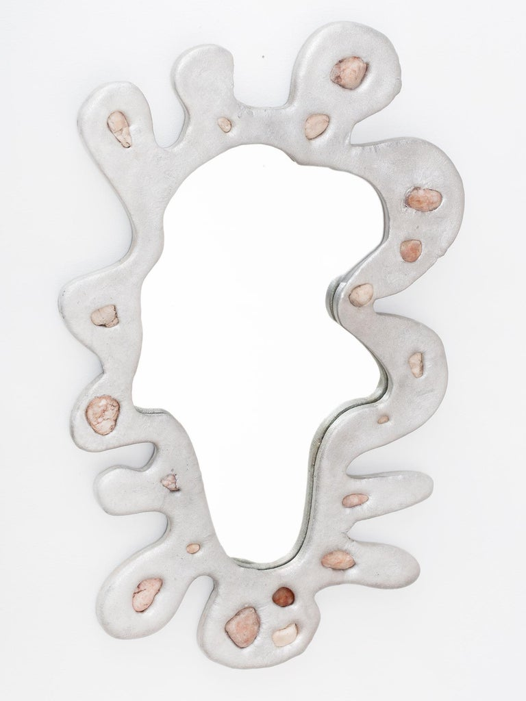 Sand-cast aluminum wall mirror in undulating splatter shape with incorporated natural stones. Made in Colombia by New York and Medellín-based artist Chris Wolston. One in stock and available now, more available to order in 8-10 weeks. From an