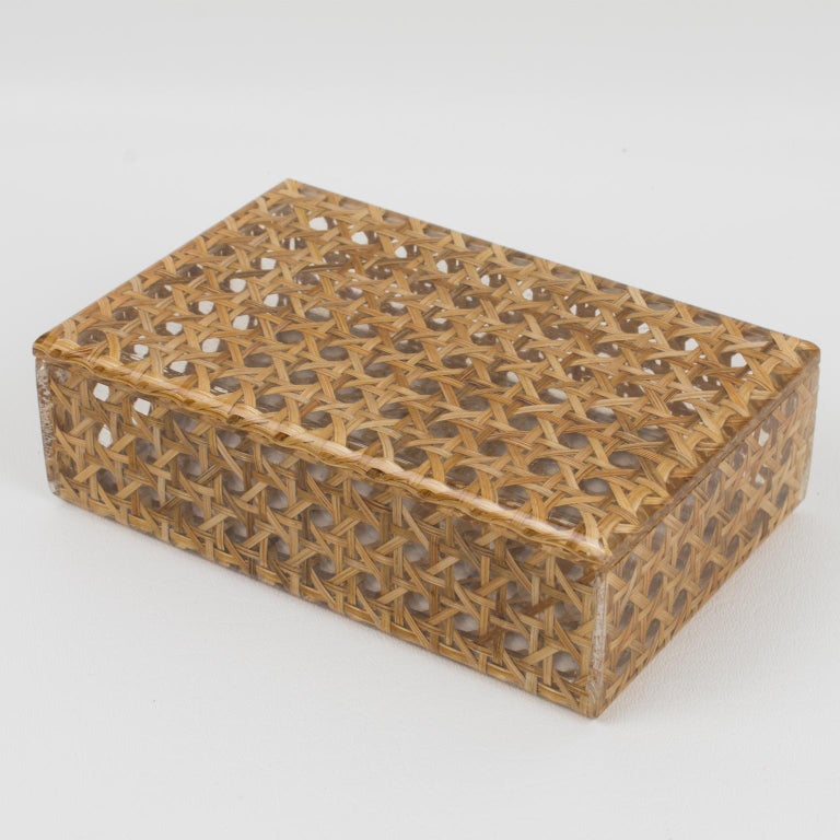 A charming 1970s Lucite decorative box designed for Christian Dior Home Collection. Large rectangular shape with real rattan (or wicker) cane work embedded in the crystal clear Lucite. Great accessory for any modern interior. Measurements: 6.13 in.