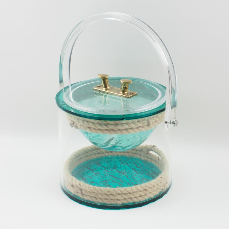 Stunning barware ice bucket designed for Christian Dior home collection, in the 1970s. Rounded shape with tall handle, featuring real rope embedded in the crystal clear Lucite, with a brass metal handle on the lid in a boat-fittings-like shape. The