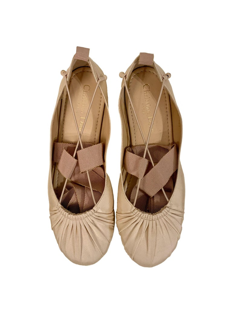 These pre-owned gorgeous ballerina flats are crafted in a nude color grain canvas.  They feature grosgrain ribbon laces which wrap nicely around the ankle. A lightly padded leather insole and a flexible suede sole with rubber pods.    Collection :