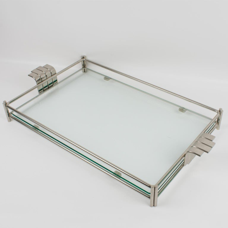 Sophisticated 1980s modernist barware serving tray platter designed for Christian Dior Home Collection. Large rectangular butler shape builds with silvered metal framing and thick glass slab insert. Elegant raised handles on the sides. The engraved