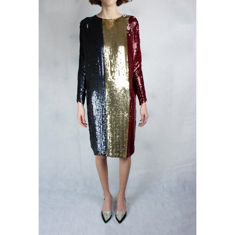 Christian Dior Homage to France cocktail dress is constructed with a silk material decorated with single knotted sequins. Featuring long batwing sleeves with zips at the cuffs and a round neckline.