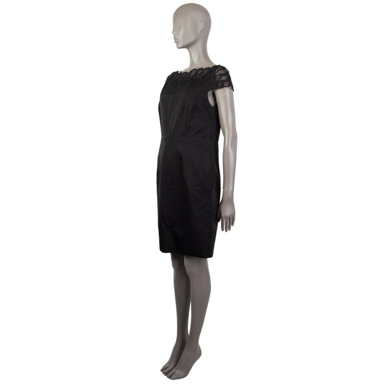 Christian Dior sheath dress in black wool (57%) silk (43%) with an embroidered bateau neck, short sleeves, above knees, close fit and a slit in the back. Closes with a concealed zipper in the back. Lined in a black fabric silk (100%). With a view