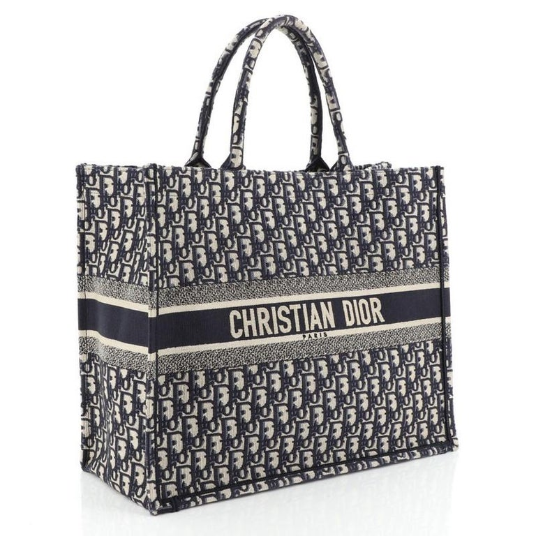 This Christian Dior Book Tote Oblique Canvas, crafted in blue oblique canvas, features dual rolled handles and Christian Dior lettering at front. It opens to a blue oblique canvas interior.   Condition: Very good. Loss of shape on exterior, minor