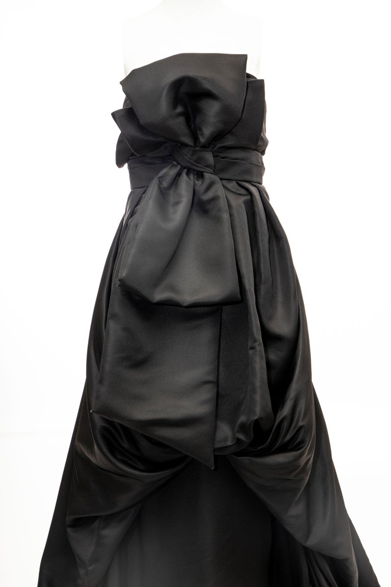 Christian Dior by Gianfranco Ferré, Circa: 1990's black silk strapless evening gown with bow accent at front; draped overlay, train at hem, inbuilt corset and concealed zip & snap closure at side.    FR. 38, US. 6  Bust: 34, Waist: 31, Hip: 44,
