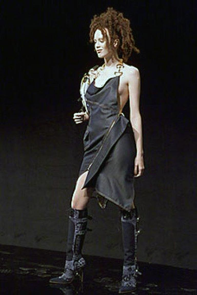 Black Christian Dior by John Galliano early iconic Spring 2000 runway collection featuring cowl neckline halter style dress enhanced by gold-tone logo hardware at straps.  Asymmetrical hem and zipper gold-tone closure at side.  Fully lined.  Rare to