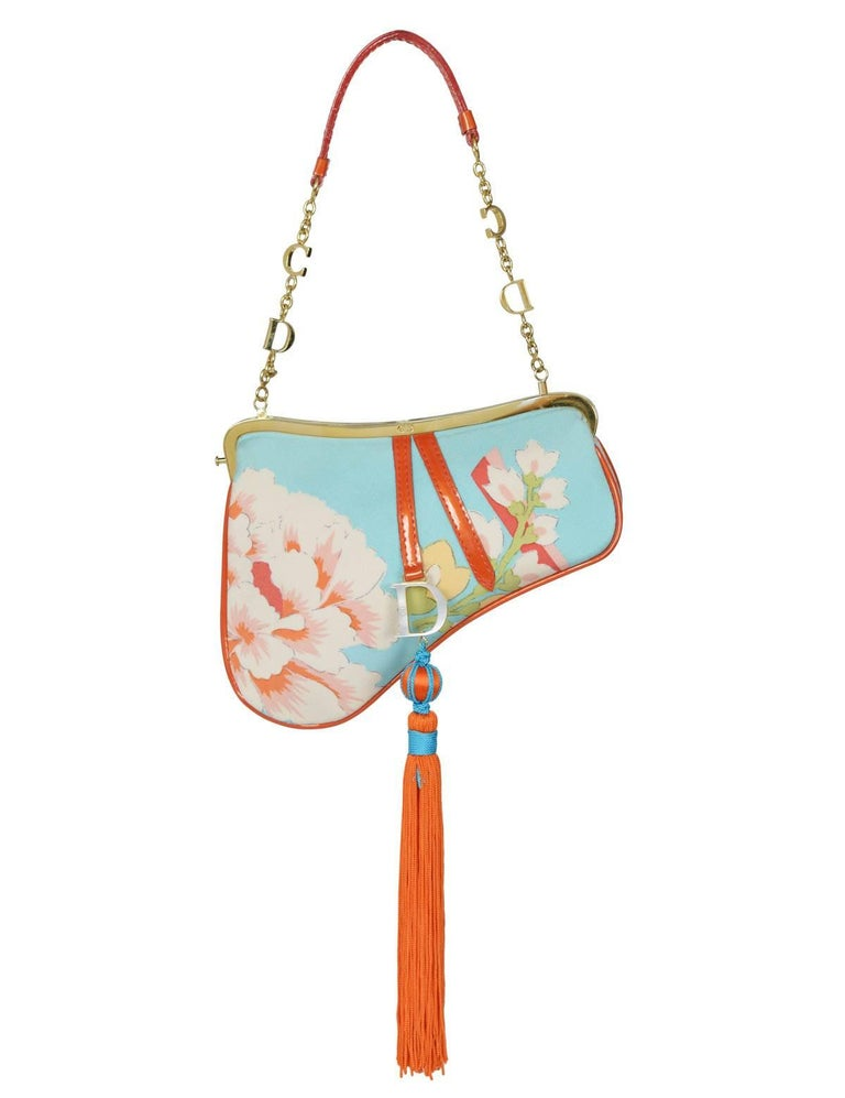 Christian Dior by John Galliano silk floral mini saddle evening bag with large red orange tassel, CD gold hardware and red trim. Dior print on backside. Collection AW 2003.