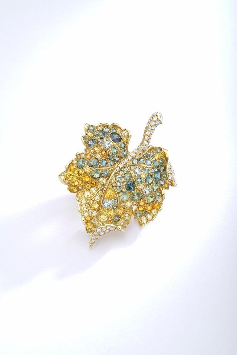 8 Karat Two-Color Gold, Diamond and Colored Sapphire Leaf Brooch, Christian Dior, France.Designed as a leaf, the body composed of round diamonds, further set with green, orange and yellow sapphires, gross weight approximately 14 dwts, signed