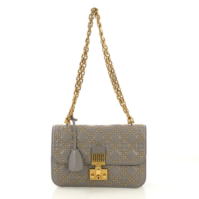 This Christian Dior Dioraddict Flap Bag Cannage Studded Leather Medium, crafted in gray cannage studded leather, features chain link shoulder strap and gold-tone hardware. Its Dioraddict clasp closure opens to a gray suede interior with zip and slip