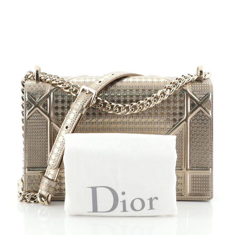 This Christian Dior Diorama Flap Bag Cannage Embossed Calfskin Medium, crafted in gold cannage embossed calfskin, features a graphic-style cannage quilt design, chain strap with leather pad, and gold-tone hardware. Its crest-shaped clasp closure