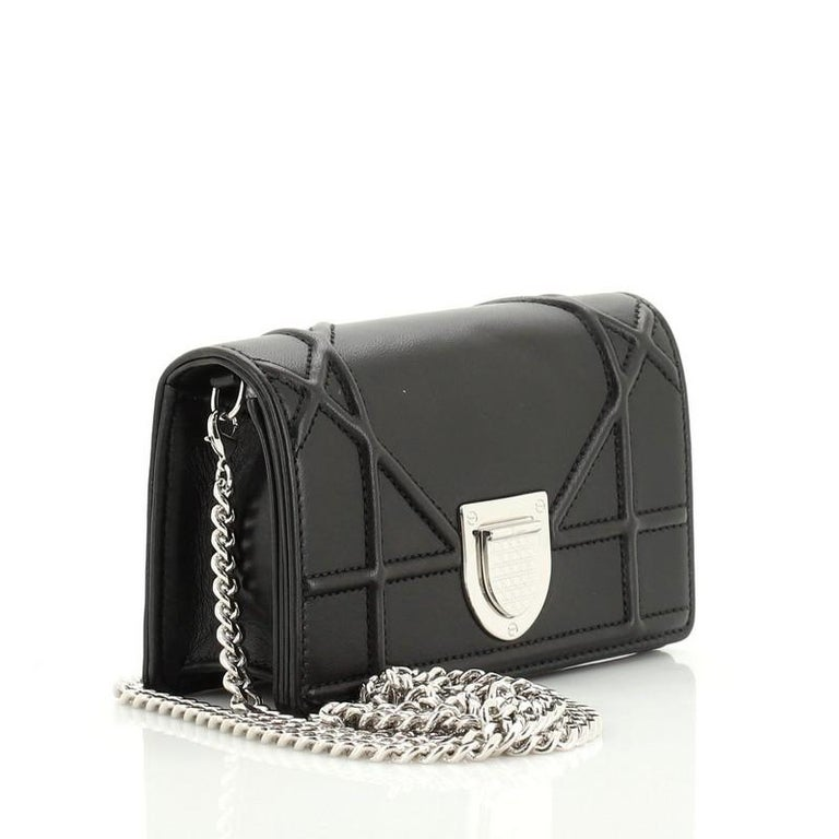 This Christian Dior Diorama Flap Bag Leather Baby, crafted in black calfskin leather, features an oversized cannage quilt design, chain strap with leather pad, and silver-tone hardware. Its crest-shaped clasp closure opens to a black leather