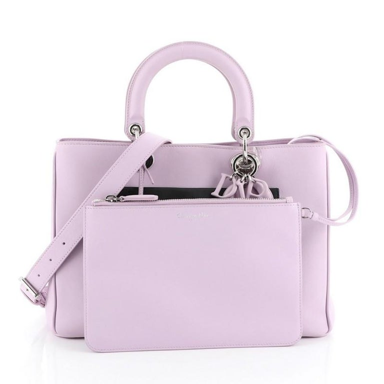 This Christian Dior Diorissimo Pocket Tote Leather Medium, crafted from purple leather, features short dual handles with Dior charms, side snap buttons, exterior front and back flap pockets, protective base studs and silver-tone hardware. Its